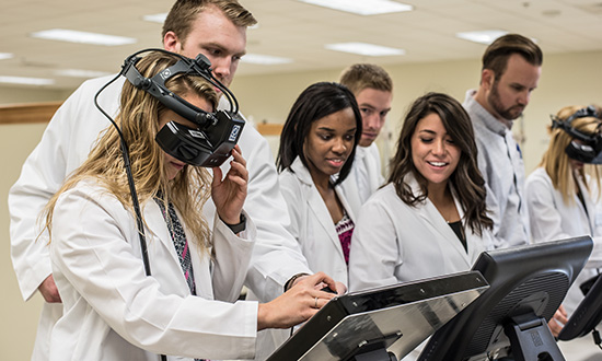 optometry students in the lab using equipment